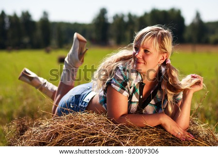 Country girl on straw bale. - stock photo