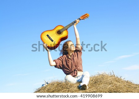 Country girl playing guitar at haystack. woman against blue summer sky. musician keep instrument above head - stock photo