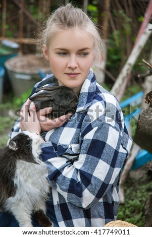 country girl sitting in the yard, dreaming and holding a rabbit in her hands, on her lap cat, looks at her - stock photo