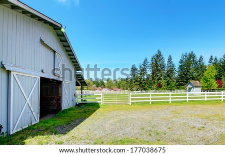 Country horse farm with wooden fence and stable. - stock photo