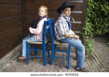 country-kids sitting backwise to each-other - stock photo