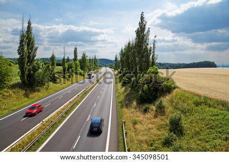 Country landscape with highway leading poplar alley next to a cornfield. Motion blur speeding cars. White truck coming from afar. View from above. Summer sunny day. - stock photo
