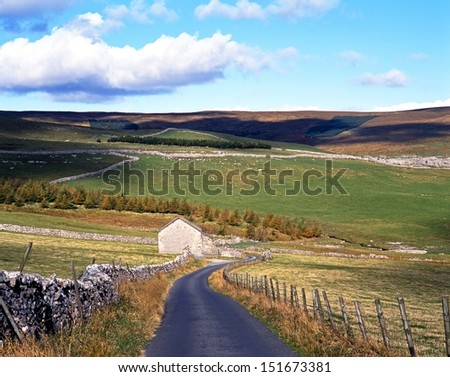 Country lane edged with dry stone walling, Yorkshire Dales, North Yorkshire, England, UK, Great Britain, Western Europe. - stock photo