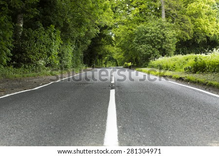 Country lane with white line markings - stock photo
