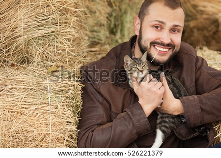 Country life concept. Young smiling relaxed man in brown leather jacket sitting near straw bales and holding little cat. Copy-space. Close up. Outdoor shot