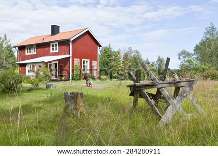 Country life during summertime period. Sawhorse, chopping block, dog and a Falu red painted house.  - stock photo