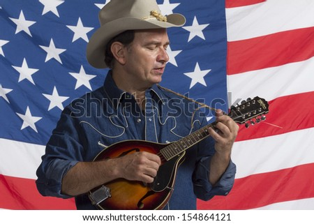 Country man playing mandolin in front of American flag, horizontal