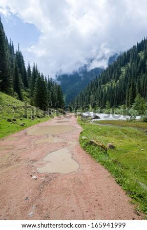 Country mountain road after rain. Kyrgyzstan - stock photo