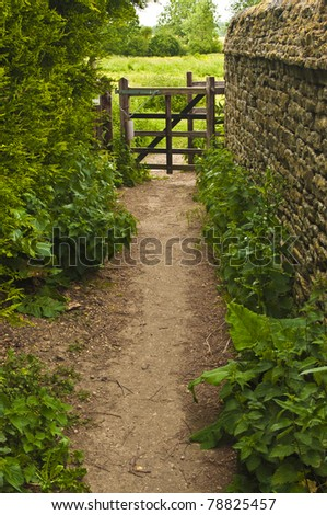 Country path with a gate at the end - stock photo