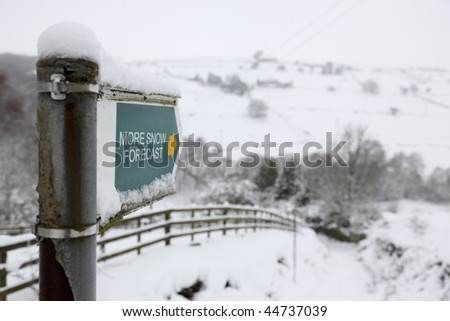 Country pathway direction sign reading more snow forecast