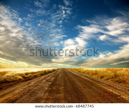 Country road and beautiful cloudscape - stock photo