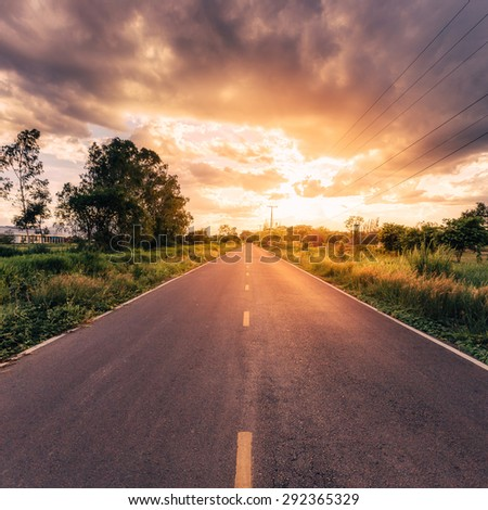 country road and field with beautiful sunset vintage - stock photo