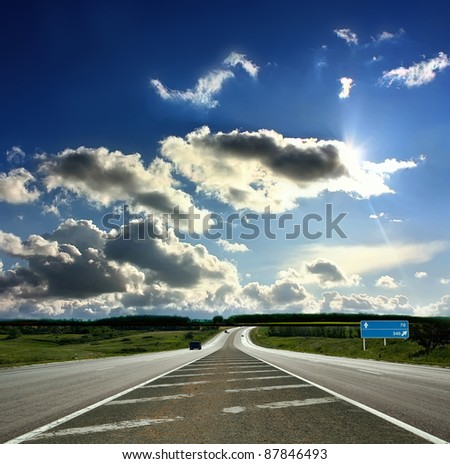 Country road and fields on the background of the blue - stock photo