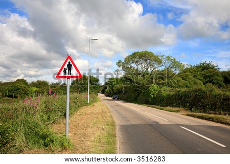 Country road and pedestrians in road sign, Cornwall, UK. - stock photo