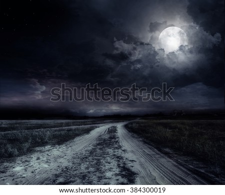 country road at night with large moon - stock photo