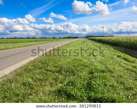Country road, farmland and wind turbines in Flevoland polder, the Netherlands - stock photo