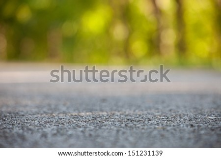Country road from the ground level - shallow depth of field and trees bokeh. - stock photo