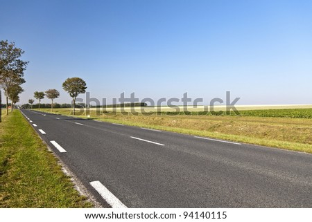 Country road in a beautiful agricultural area in northern France - stock photo