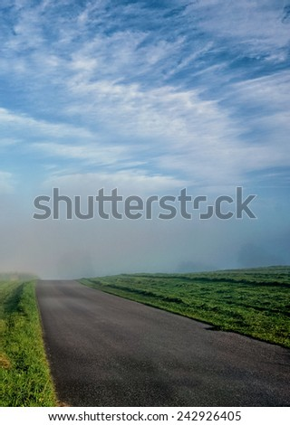 country road in morning fog with blue sky and clouds - stock photo