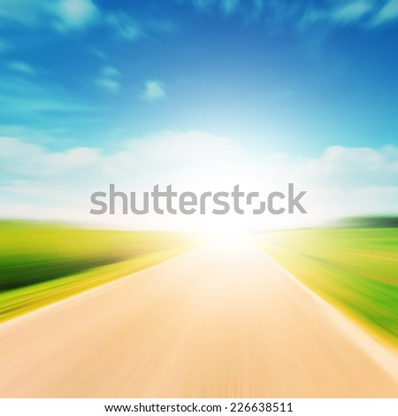 Country road in motion blur and sunlight. - stock photo
