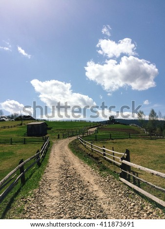 Country road in the Carpathian Mountains. Beautiful landscape, green grass, small barns and road in clouds, this is what awaits the traveler coming to the mountain Kichera in the Carpathians. - stock photo