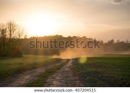 Country road landscape in sunset. Sun rays through the dust. - stock photo