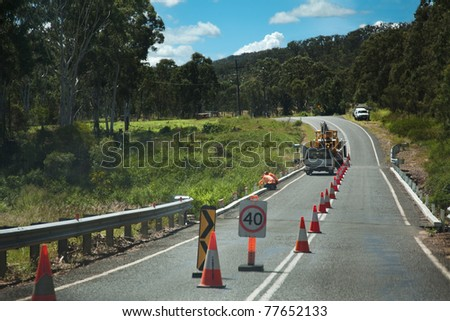 country road lane closed repair construction works machinery workers traffic closed and restricted slow - stock photo