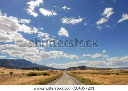 Country road leading off in the mountain range. - stock photo