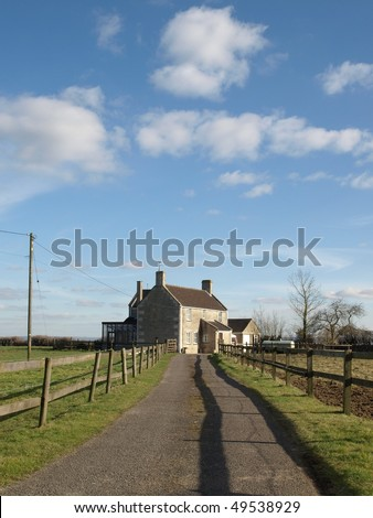 Country Road Leading to a Farmhouse - stock photo