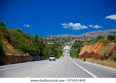 country road leading up to mountains in Crete, Greece - stock photo