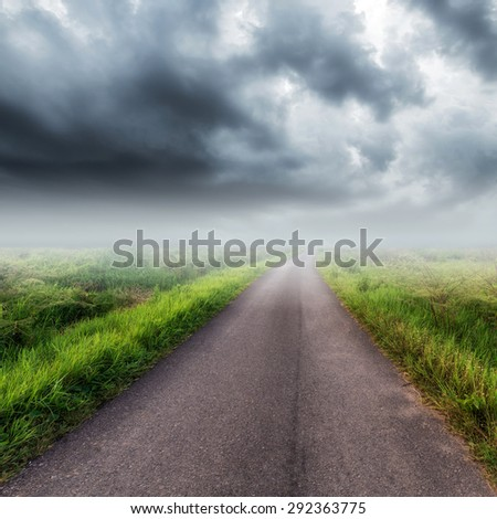 Country road on field and storm clouds or rainclouds