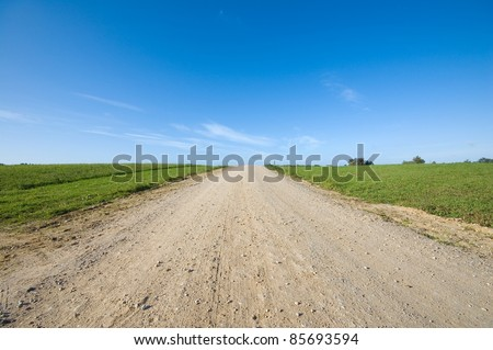 Country road running through field - stock photo