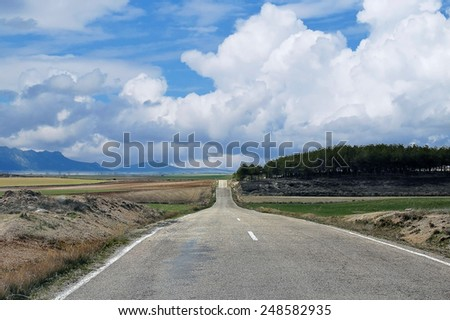 country road that is lost in the horizon - stock photo