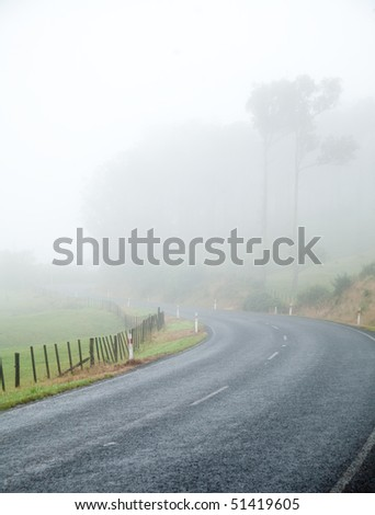 Country road turn on a foggy day - stock photo