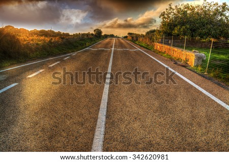 country road under a dramatic sky in hdr tone mapping effect - stock photo