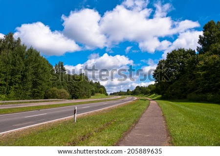 Country Road up the Hill with Trees Around and Cloudy Sky - stock photo