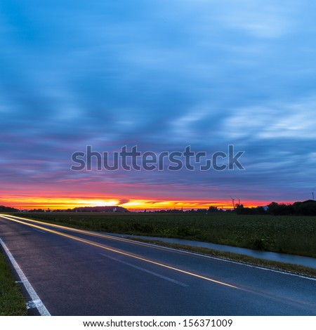 country road  with Cloudy Sky in the light of the dawn sunset  - stock photo