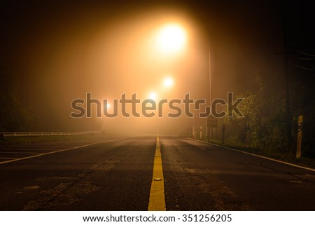 Country road with night light among the mist. - stock photo