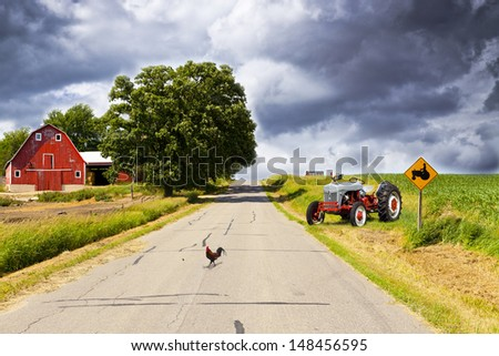 Country Road With Red Barn and Tractor On Side - stock photo