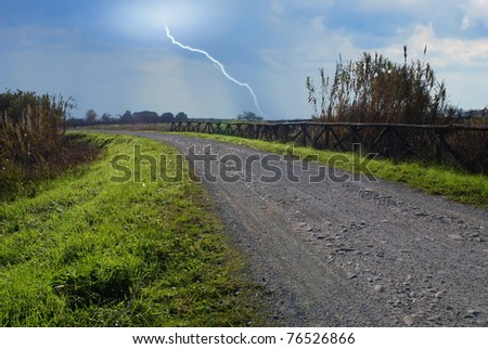 country road with storm incoming - stock photo