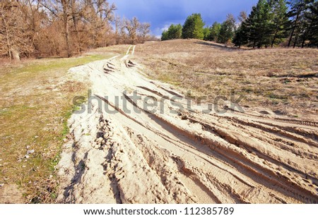 country sand road in sunny autumn day - stock photo