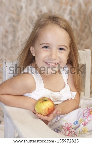 Country setting for this school girl with a smile and holding an apple - stock photo