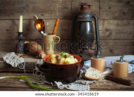Country still life with an old kerosene lamp, pan with potatoes and chicken hearts, bread and spring onions. Selective focus and toned.  - stock photo
