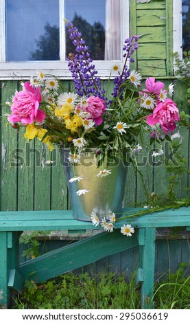 Country still life with flowers in a bucket on green bench against old house background, vertical - stock photo
