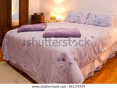 country style bedroom with double bed,wooden armoire and floor and bedside lamp - stock photo