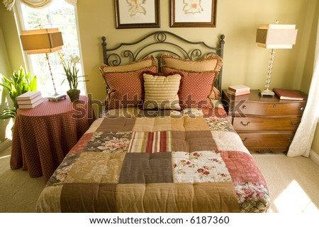 Country style bedroom with quilted bed cover. - stock photo