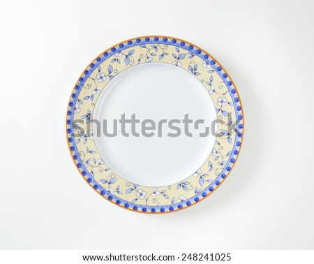 Country style dinner plate with floral design border and brown trim - stock photo