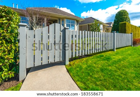 Country style long wooden fence with the gate, wicket and a house behind. Country style long wooden fence with nicely trimmed grass. - stock photo