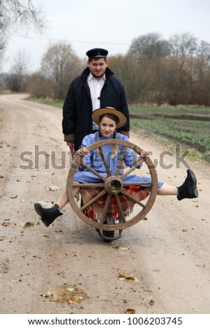 Country style man drives in a wheelbarrow the woman with cartwheel in hands on rustic road outdoor - peasant lifestyle