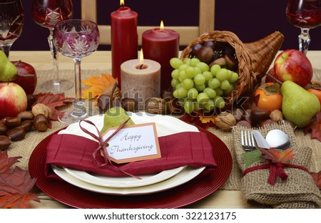 Country style rustic Thanksgiving table with place setting, cornucopia, candles and Autumn fruit centerpiece.  - stock photo